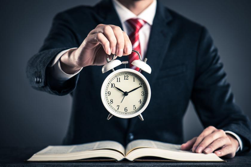 Часы, стоящие на столе, и мужчина, сидящий в костюме на стуле
