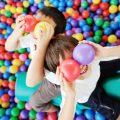 Дети лежат в сухом бассейне среди разноцветных пластиковых шаров