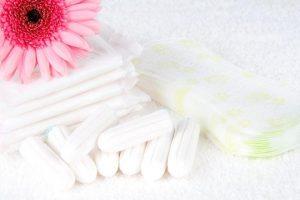 Гигиенические прокладки и слабые тампоны на белом полотенце