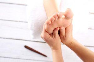 Косметолог давит рецепторы на ступнях