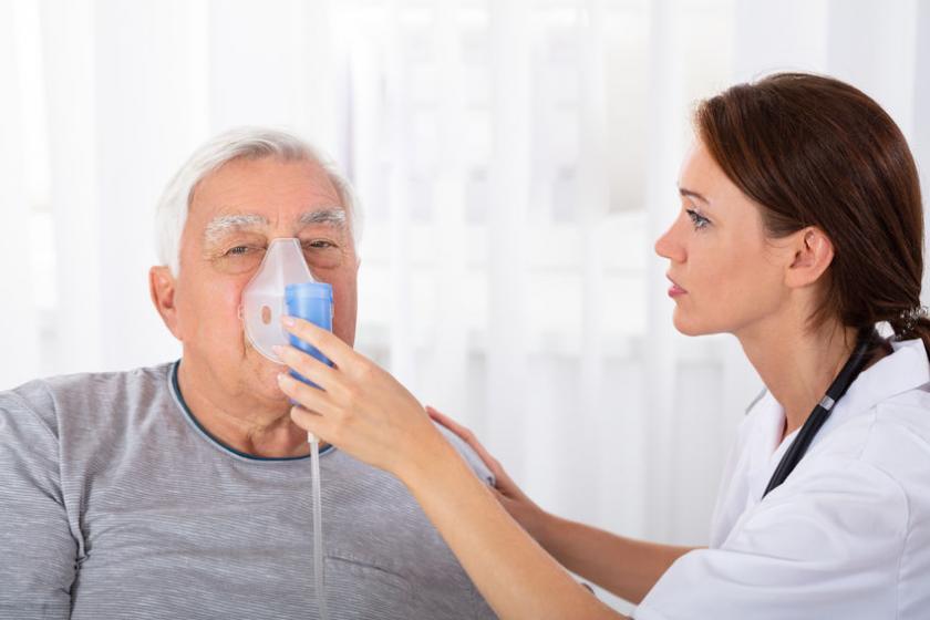 Медсестра помогает пациенту пройти пассивную кислородную терапию.