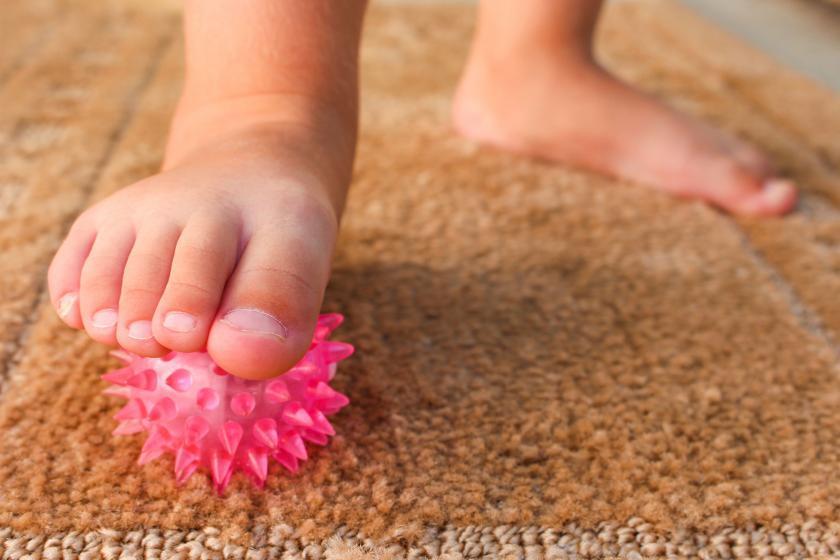Ножки младенца, стоящие на силиконовой игрушке