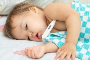 Ослабленный ребенок с термометром в подмышке