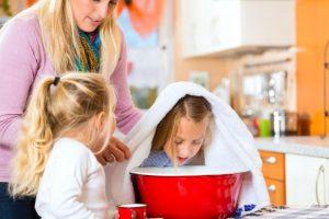 Ребенок с полотенцем на голове, склонившись над тазом с горячей водой