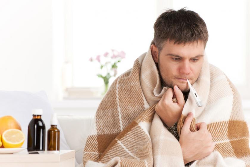 Укрытый одеялом мужчина измеряет температуру