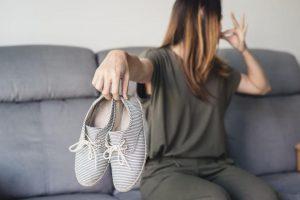 Женщина держит в руке грязные туфли
