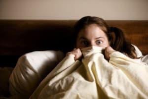Испуганная девушка смотрит из под одеяла