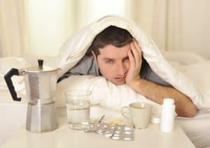 Мужчина под одеялом, рядом таблетки, чашка и стакан