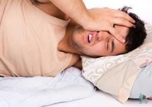 Мужчина в постели мучается похмельем
